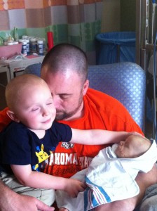 Austin holds his sons Tucker, left, and Greyson, right. Greyson, the little Lion Man, died when he was six months old.