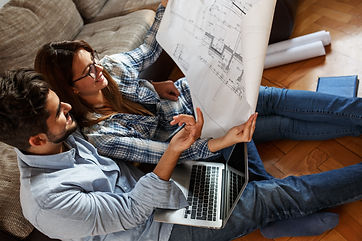 Young couple examining blueprints of the