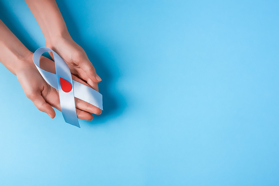 the blue ribbon awareness with red blood drop in woman hands isolated on a blue background