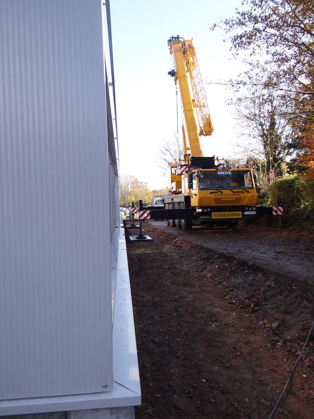 De achter gevel en linker zijgevel. De kraan staat klaar om de dakplaten te leggen.