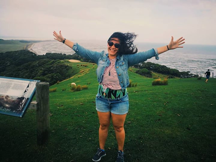Vanessa Immink with arms spread out wide at Puponga/Farewell Spit lookout