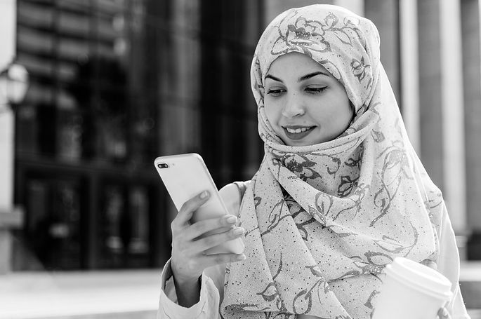Photo of a young woman texting on a smart phone.