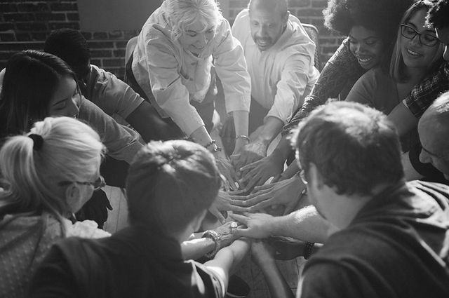 Photograph of people standing in a circle, putting their hands together in the middle of the circle. These people are all different ages, races and genders.