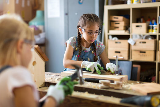 Two young girls doing woodwork in a work
