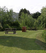 A view of a grassed area with two picnic benches and a barbeque.