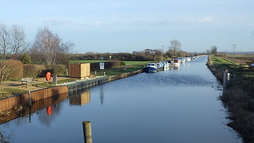 A long view of the river Great Ouse in to the distance with boats lining the left bank.