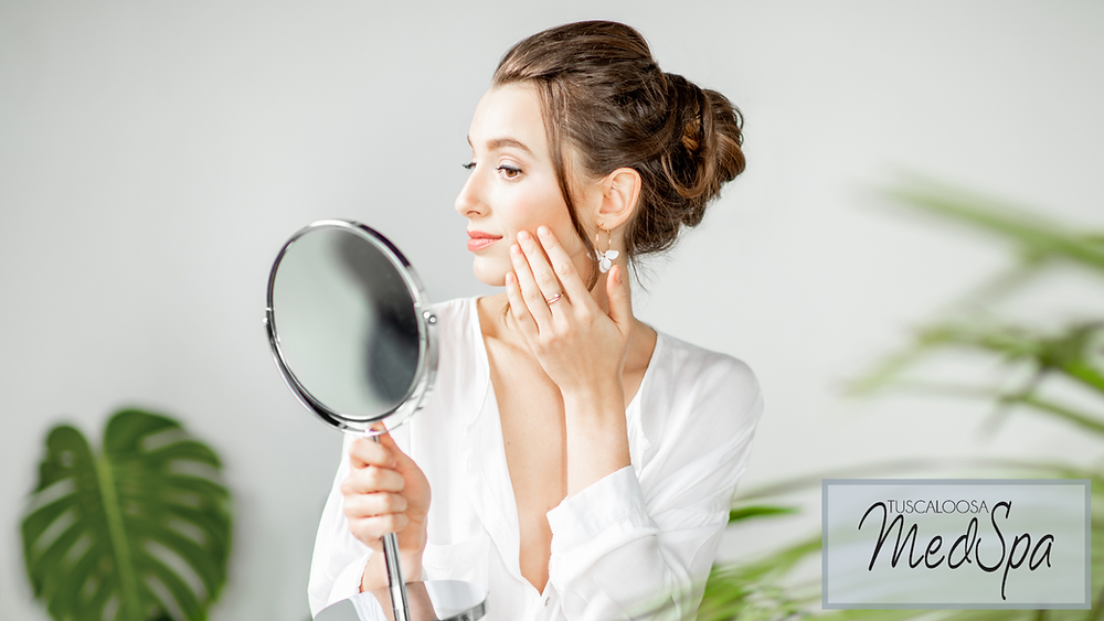 woman with youthful skin looking happily into a mirror after receiving her 2021 beauty treatments at Tuscaloosa Medspa