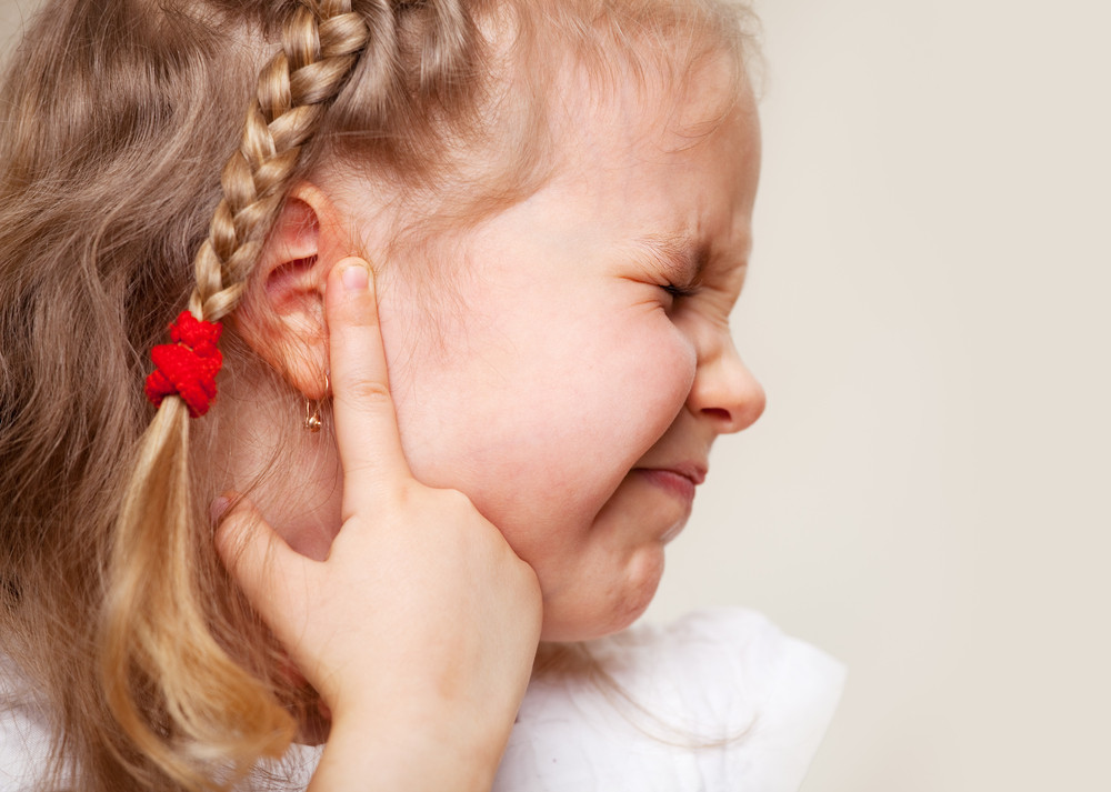 child touches ear while in pain