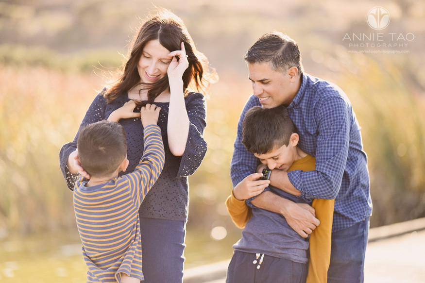 East-Bay-lifestyle-family-children-photography-hugging-and-son-playing-with-moms-necklace