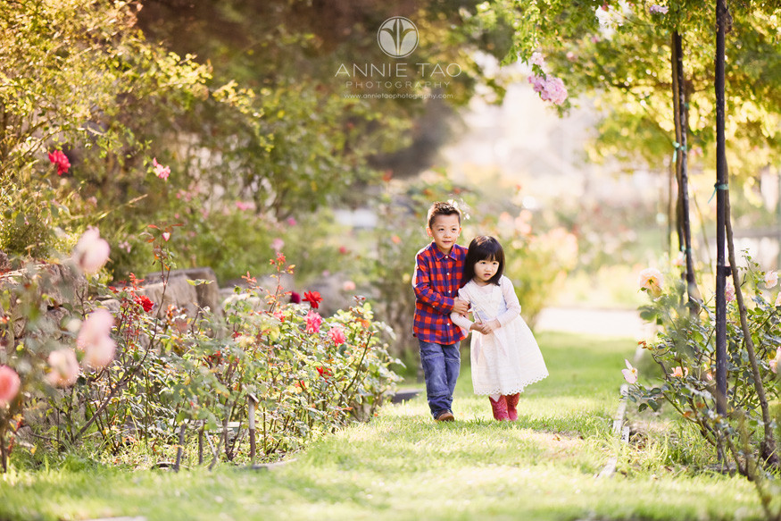 East-Bay-lifestyle-children-photography-little-boy-holding-frightened-younger-sisters-arm-in-rose-garden