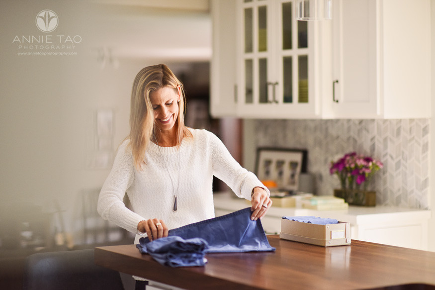 East-Bay-commercial-photography-home-organization-woman-folding-cloth-napkins-in-kitchen