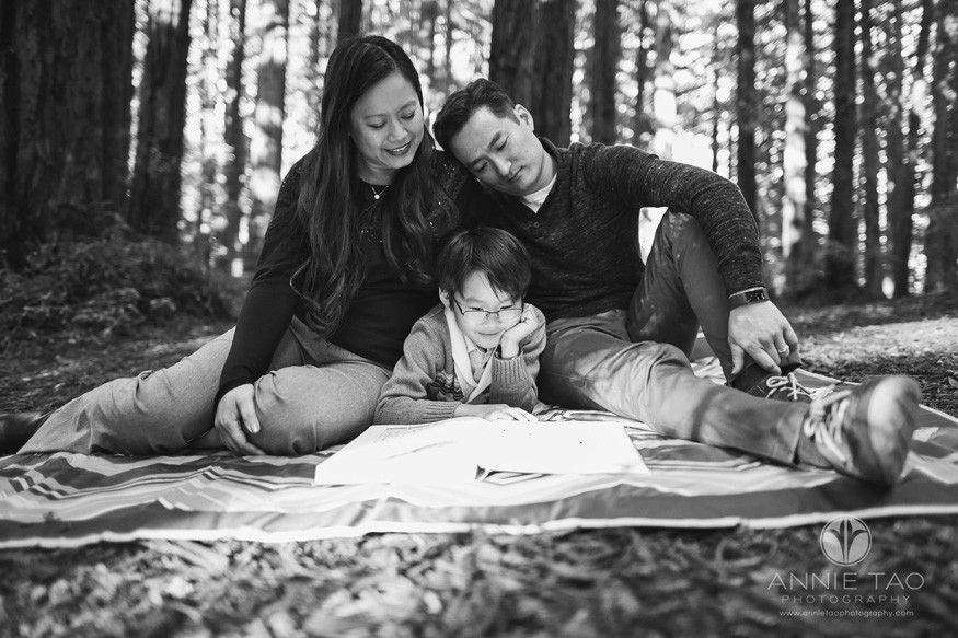 East-Bay-lifestyle-family-photography-family-reading-comic-book-with-son-in-forest-BxW