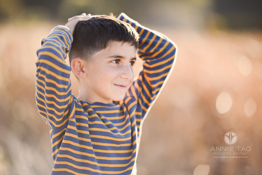 East-Bay-lifestyle-children-photography-young-boy-smiling-with-arms-on-head-in-golden-sunlight