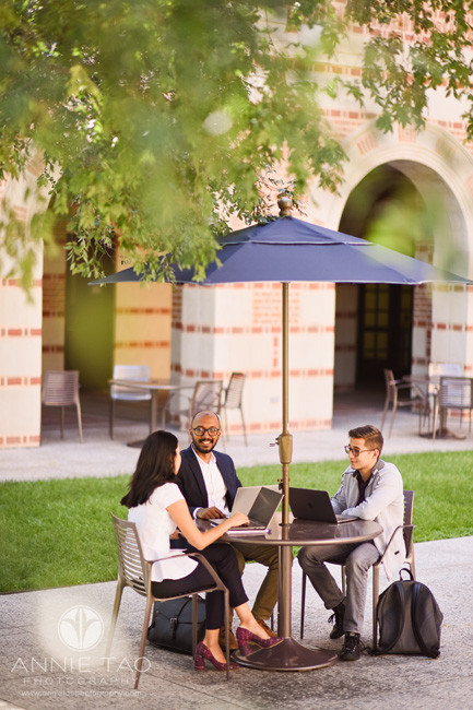 Commercial-Photography-Rice-Business-School-three-students-working-together-on-laptop-in-courtyard-distant-view