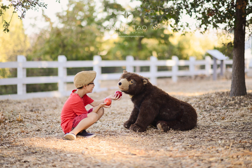 east-bay-styled-children-photography-boy-in-red-feeding-apples-to-bear