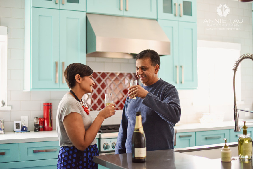 East-Bay-lifestyle-home-photography-couple-toasting-wine-glasses-in-kitchen