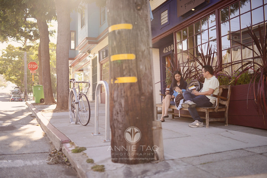 San-Francisco-lifestyle-newborn-photography-family-sits-on-sidewalk-bench-with-sunflare