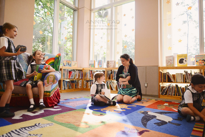 Commercial-education-photography-librarian-kneeling-next-to-student-in-reading-room-of-library