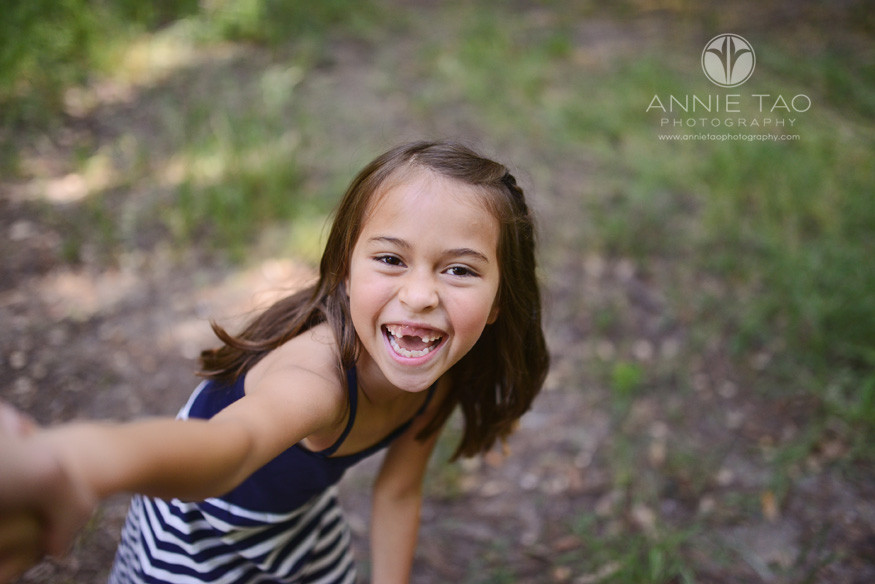 East-Bay-lifestyle-children-photography-young-girl-holding-photographers-hand-and-cracking-up