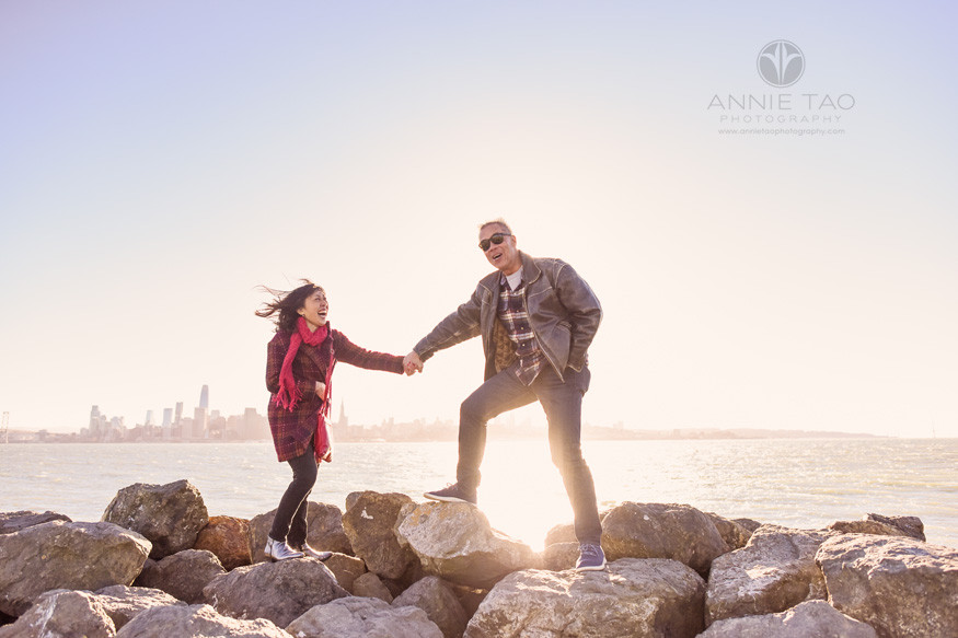 San-Francisco-lifestyle-couple-photography-husband-holding-wifes-hand-on-rocks-on-windy-day-by-bay