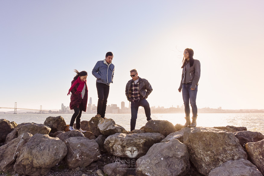 San-Francisco-lifestyle-family-photography-standing-on-boulders-by-bay-on-windy-day