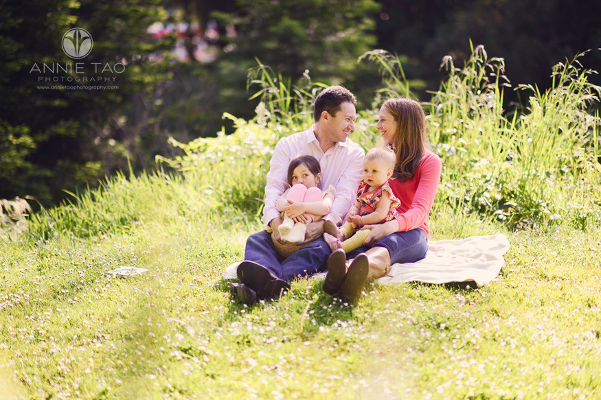 San-Francisco-lifestyle-family-photography-parents-looking-at-each-other-and-laughing-while-holding-daughters-on-grass