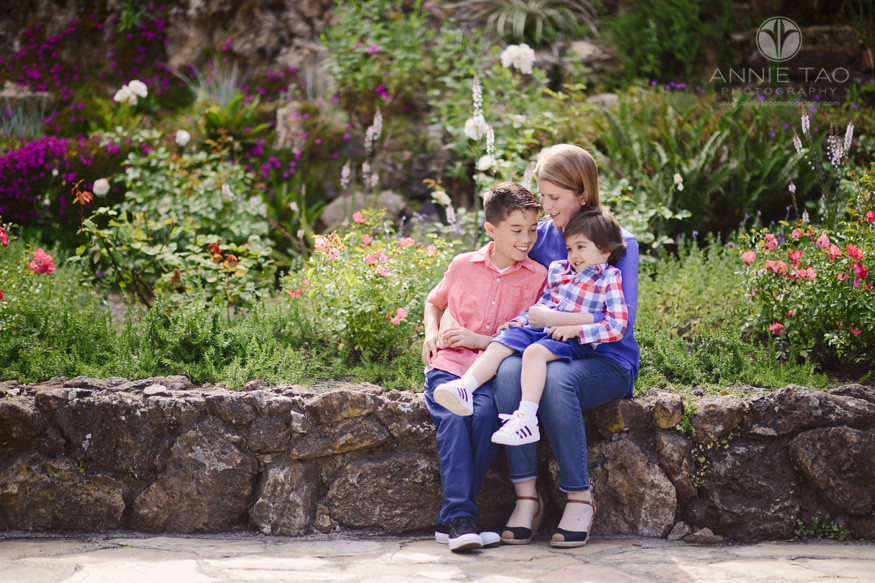 East-Bay-lifestyle-family-photography-mom-sitting-with-sons-on-rock-wall-by-garden