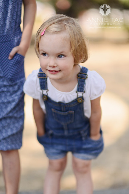 East-Bay-lifestyle-children-photography-toddler-girl-happy-with-hands-in-denim-overalls-pockets