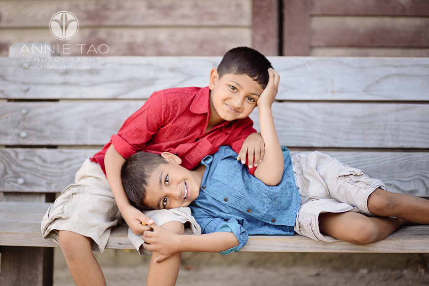 East-Bay-lifestyle-family-photography-two-brothers-laying-on-each-other-on-a-bench