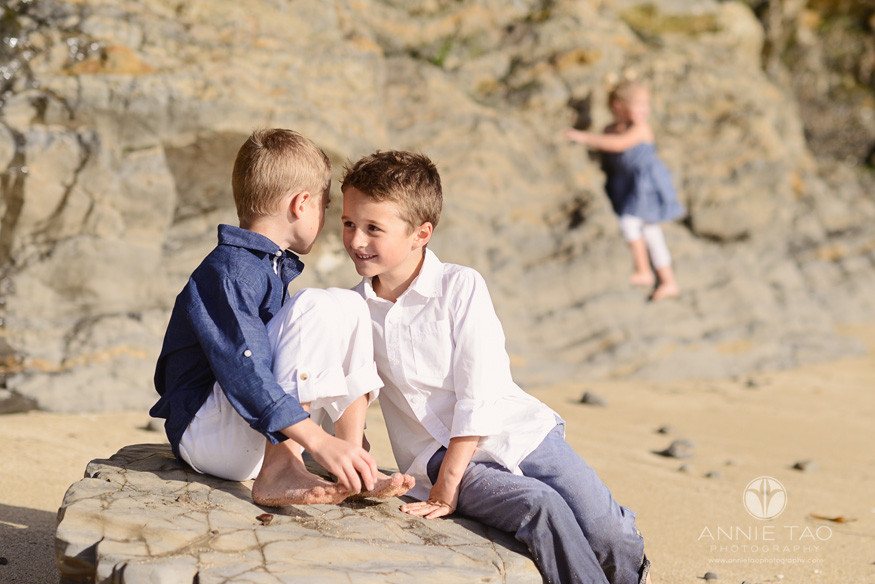 Bay-Area-Half-Moon-Bay-lifestyle-children-photography-brothers-whispering-while-little-sister-plays-in-back
