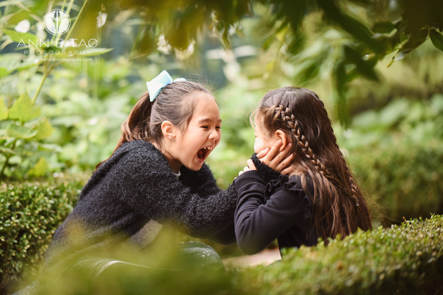 San-Francisco-lifestyle-children-photography-sisters-laughing-and-one-touches-the-younger-sisters-face