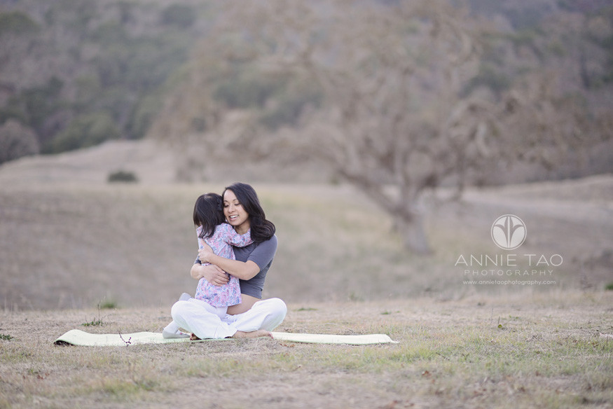 East-Bay-lifestyle-maternity-photography-daughter-hugging-pregnant-mom-among-the-hills