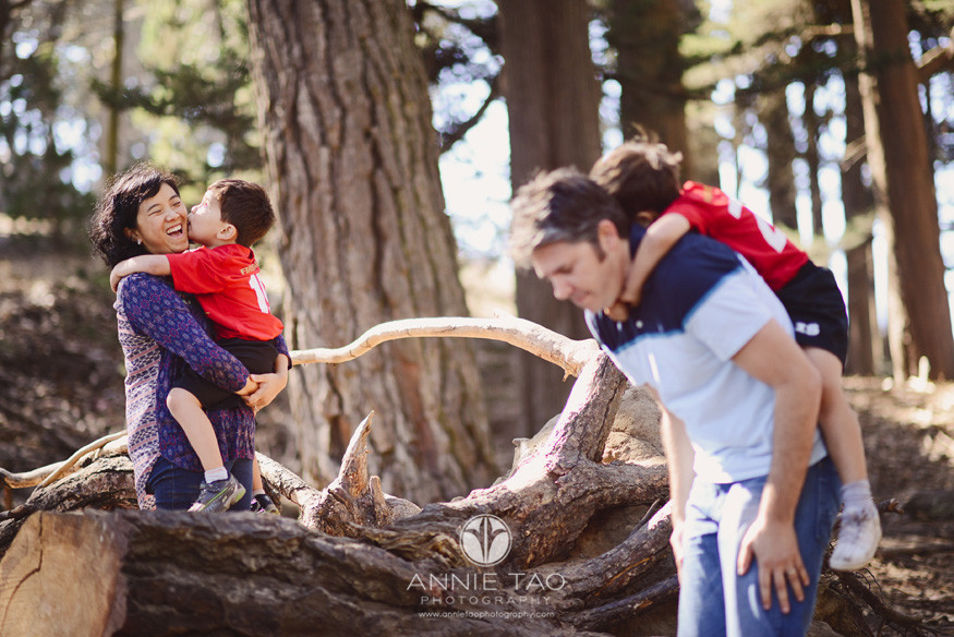 San-Francisco-Bay-Area-lifestyle-family-photography-one-son-kissing-his-mom-while-another-son-holding-on-to-his-dad