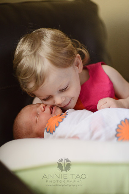 East-Bay-lifestyle-newborn-photography-toddler-girl-touching-cheeks-with-newborn-sister