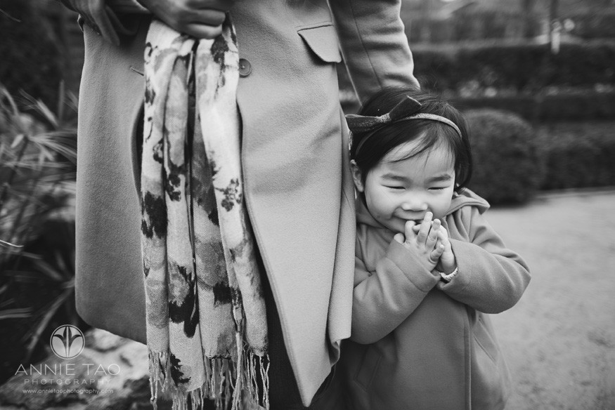 Bay-Area-Palo-Alto-lifestyle-children-photography-toddler-girl-leaning-into-mom-with-fingers-to-her-mouth-BxW