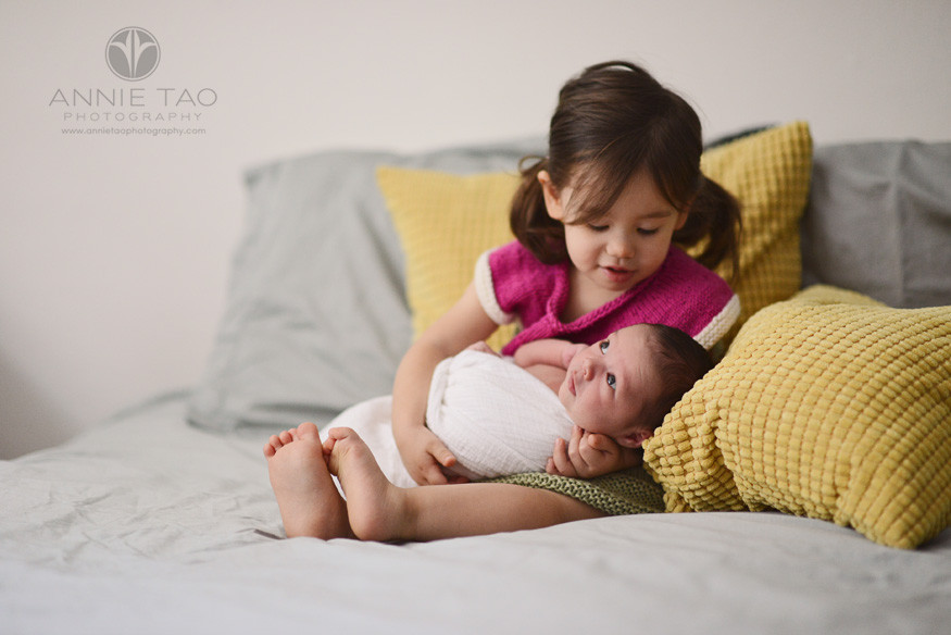 East-Bay-lifestyle-newborn-photography-baby-looking-around-while-big-sis-holds-him
