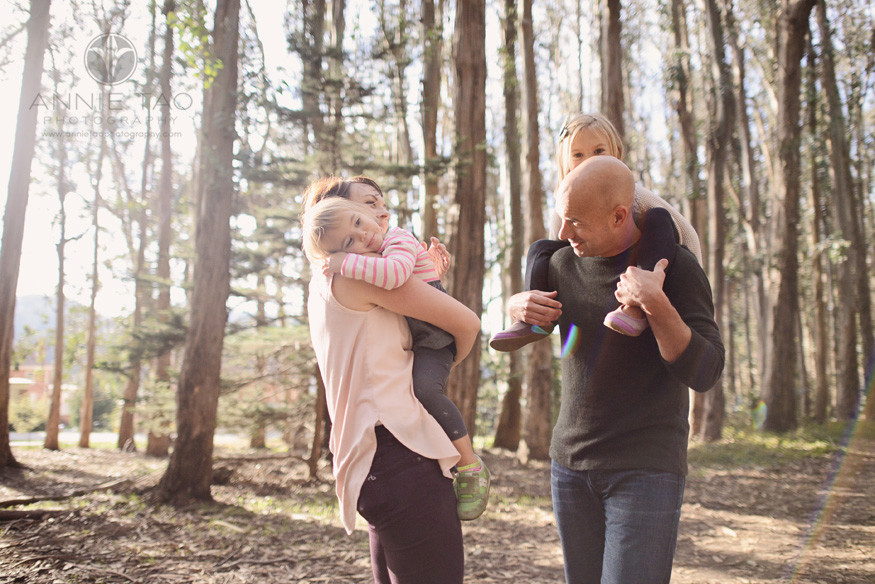 San-Francisco-lifestyle-family-photography-parents-carrying-daughters-in-woods-with-sunflare