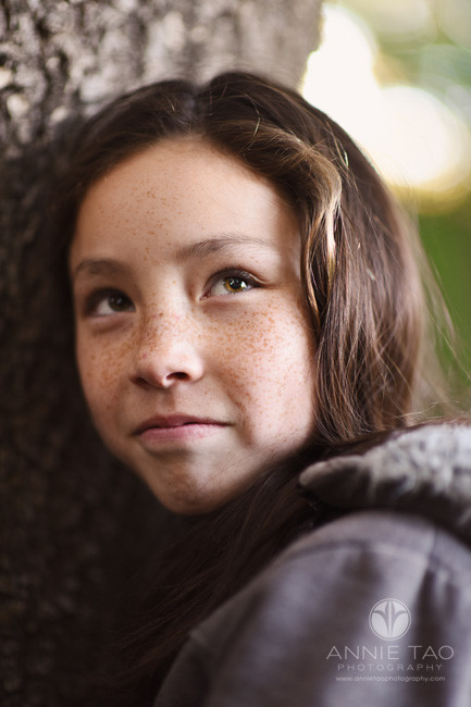 east-bay-styled-children-photography-girl-with-freckles-against-tree-glancing-upwards