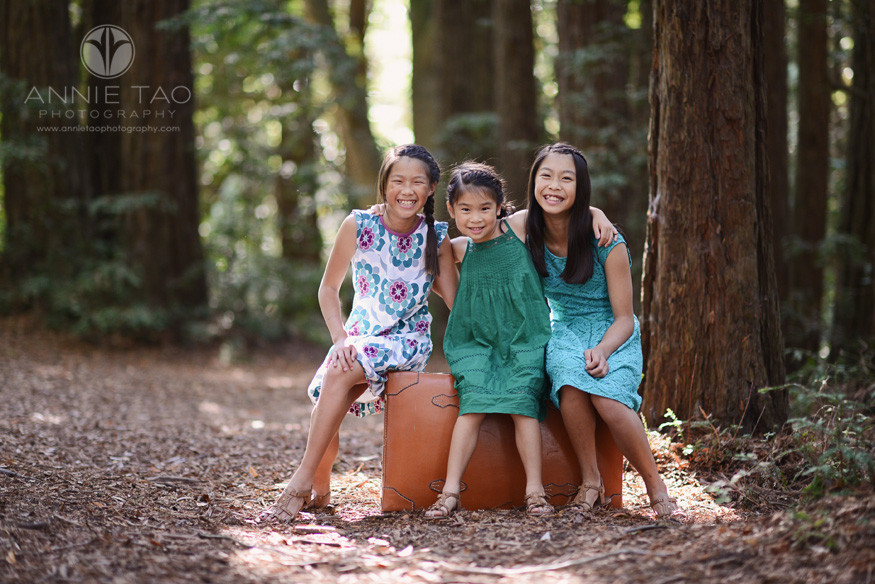East-Bay-styled-children-photography-three-sisters-sitting-on-suitcase-in-woods