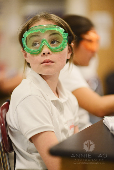 Commercial-education-photography-girl-wearing-green-goggles-in-science-class-and-looking-intently-at-board