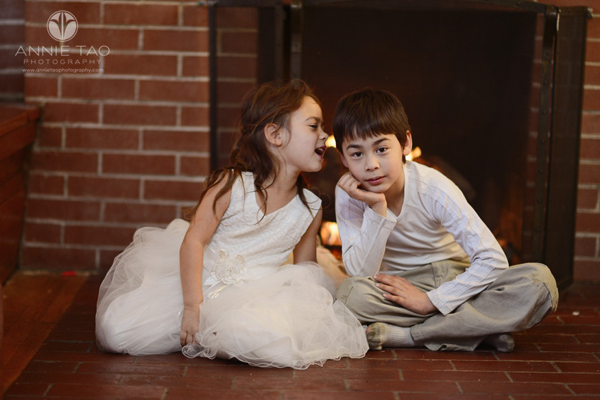 East-Bay-lifestyle-children-photography-young-siblings-whispering-by-fireplace