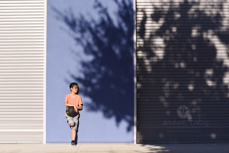 East-Bay-styled-children-photography-boy-with-basketball-at-blue-wall-and-speckled-shadows