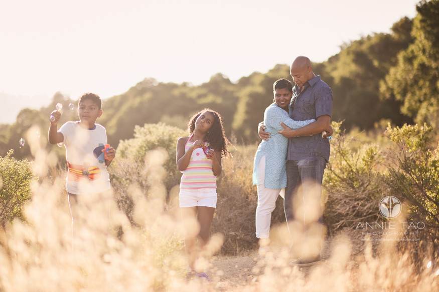 Bay-Area-lifestyle-family-photography-parents-having-a-moment-while-kids-play-with-bubbles-top-of-mountain-ridge-2