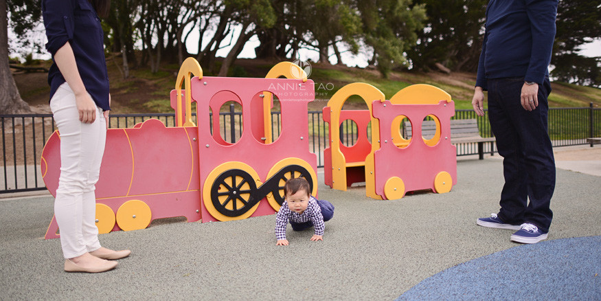 San-Francisco-lifestyle-baby-photography-parents-standing-aside-while-baby-crawls-away-from-train