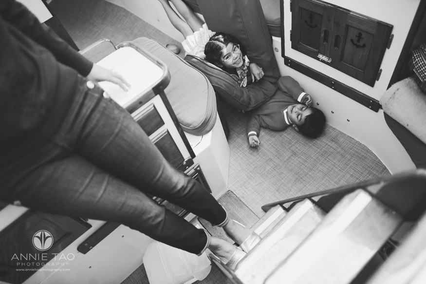 san-francisco-lifestyle-family-photography-children-playing-on-floor-of-sailboat-while-mother-watches-downward-view-bxw