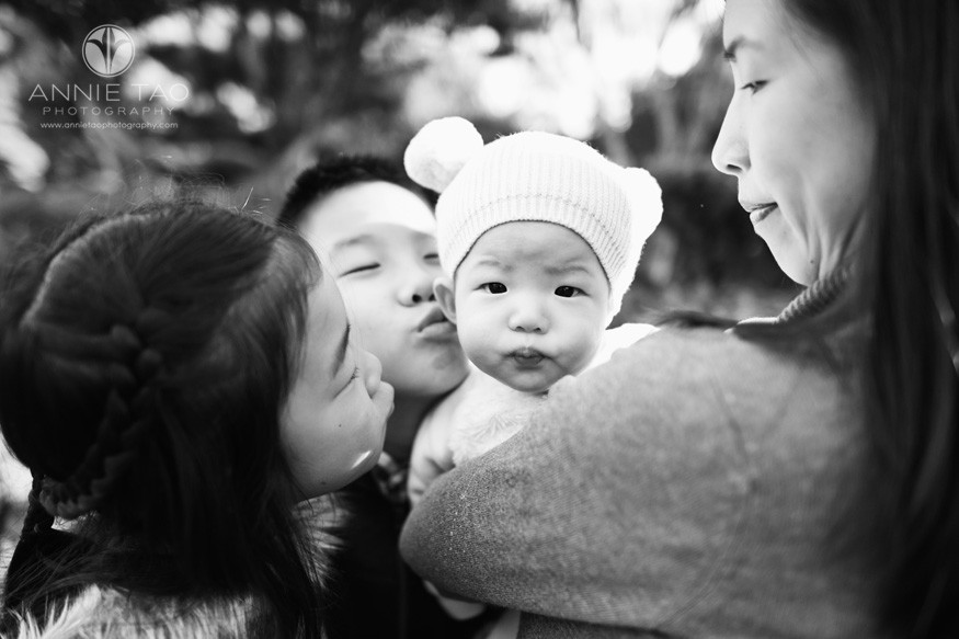 east-bay-lifestyle-baby-photography-three-siblings-kissing-perplexed-baby-in-garden-BxW