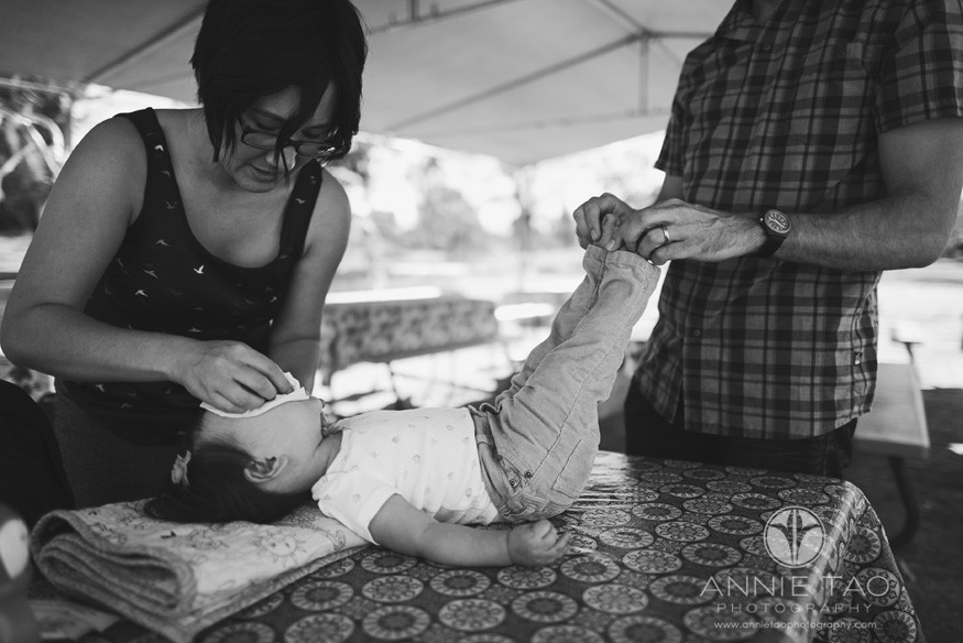 East-Bay-lifestyle-baby-photography-parents-cleaning-baby-on-table-BxW