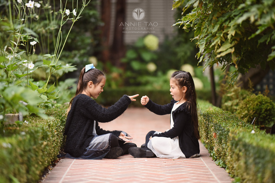 San-Francisco-lifestyle-children-photography-sisters-sitting-together-and-playing-rock-paper-scissors-in-garden