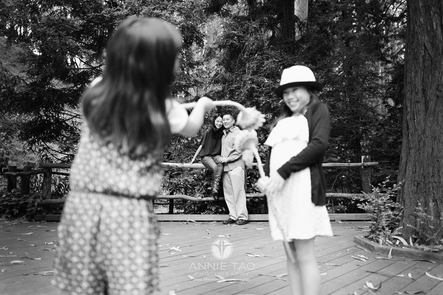 San-Francisco-lifestyle-family-photography-parents-embracing-through-daughters-playing-BxW
