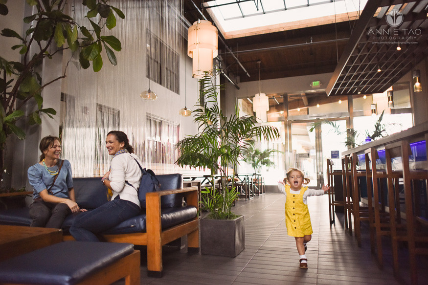 San-Francisco-lifestyle-family-photography-moms-laugh-as-toddler-girl-speeds-by-with-arms-out-in-restaurant